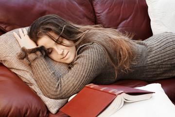 long hair girl sleeping over sofa after reading