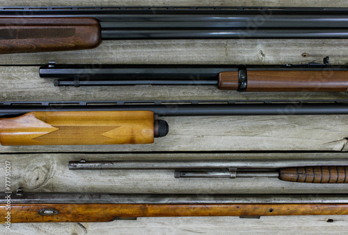 Fotobehang Persoonlijk Firearms hanging on rustic wooden background