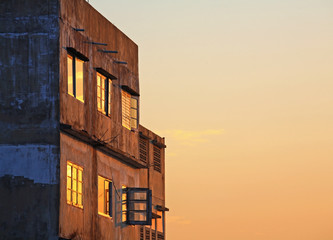 old apartment building with sunrise sky