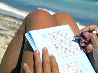 tanned girl playing sudoku on the seashore