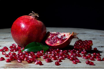 Red Pomegranate with Slices and Seeds on an Old Wooden Planks