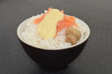 Sushi with salmon champignon and sauce in a bowl.