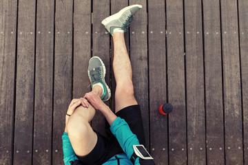 resting sportsman's legs sitting on the wooden floor