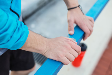 close up sportsman's hands holding railing and red sport bottle