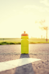 plastic sport flask with water in park at sunset