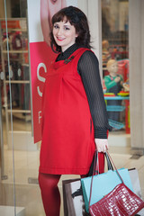 Beautiful young pregnant woman near baby store showcase