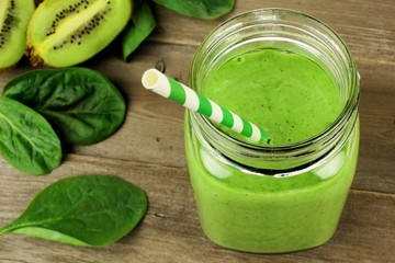 Healthy green smoothie with spinach and kiwi on wood