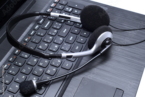 Leinwanddruck Bild Headset lying on a laptop computer keyboard
