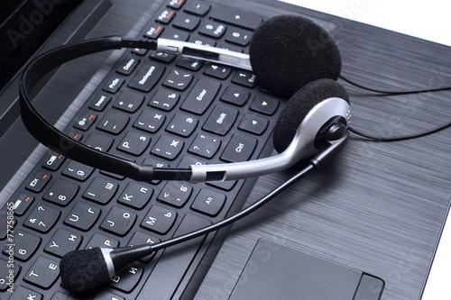 Headset lying on a laptop computer keyboard - 77758865
