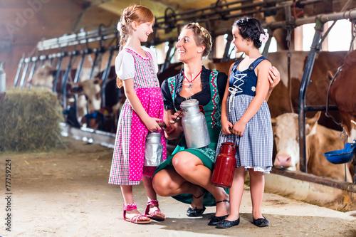 Leinwanddruck Bild Bayrische Familie mit Milchkannen im Kuhstall