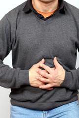 Mann hält sich Bauch vor Schmerzen,beide Hände