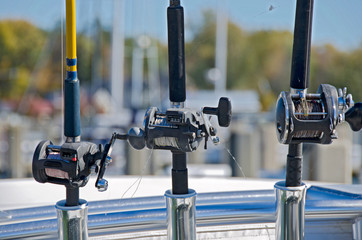 fishing rods and reels in holders on boat