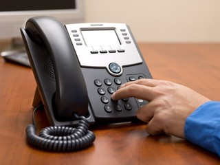 close up image of a person dialing number on landline