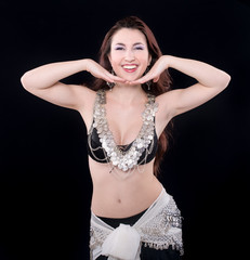 Portrait of young belly dancer againsta black background