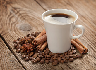 Coffee cup, anise stars, cinnamon sticks and coffee beans on old