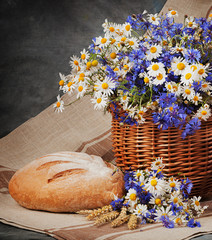 Still Daisies and cornflowers in the basket. Bread and milk on t