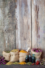 Healing herbs in hessian bags on old wooden background, herbal m