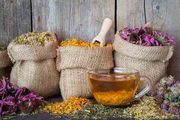 Healing herbs in hessian bags and healthy tea cup, herbal medici