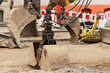 Drei Baggerschaufeln und ein Sandrüttler beim Strassenbau