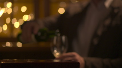 Man pouring wine into glasses. Flashing background.