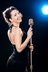 Cheerful beautiful young woman singer holding golden vintage mic