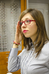 Young brunette trying glasses at the optics store