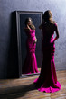 Young actress in a long dress in front of the mirror