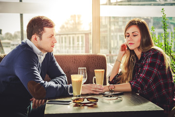Sad romantic couple holding hands at coffee shop