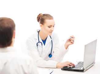 A female doctor with a laptop consulting a patient