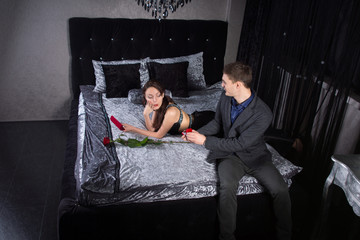 Man Offering a Ring to Girlfriend at the Bedroom