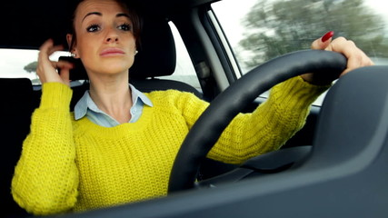 woman adjusting hair and makeup while driving car
