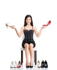 Young and attractive woman choosing shoes isolated on white