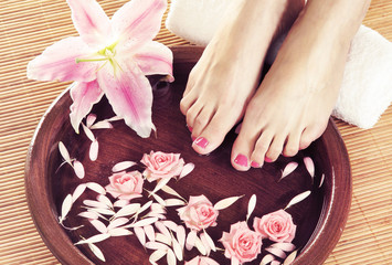Spa background with a beautiful legs, flowers, petals and cerami