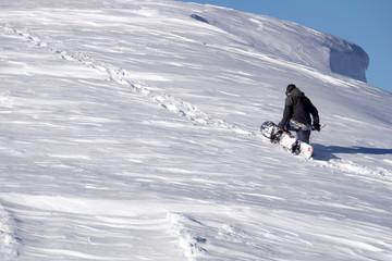 Snowboarder climbing a snowy mountain