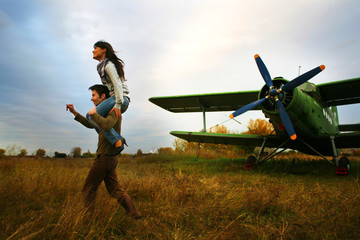 Romantic young pair outdoors near the plane. Old time