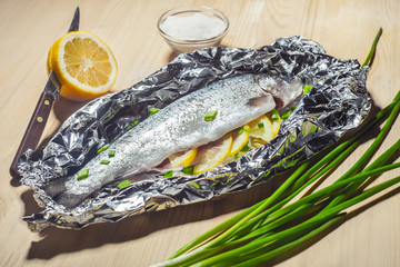 baked in foil fish on a wooden table