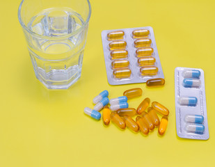 Water glass  and medicaments on yellow