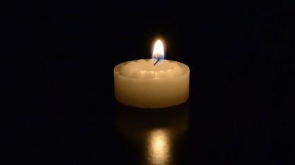 A single tea light candle burning