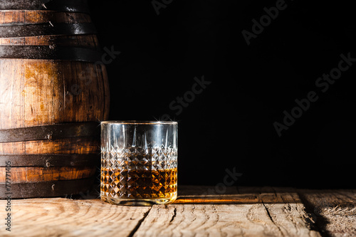 Strong alcohol on a wooden table and barrel - 77771405