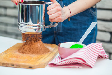 Hand sifts the flour and cocoa  through a sieve