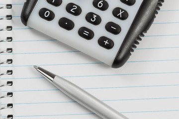 Hand Held Calculator and Pen on Notepad Paper