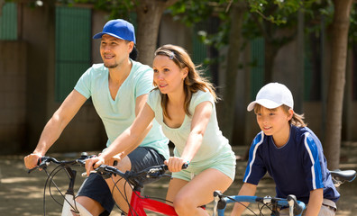 cheerful family of three cycling on city street