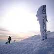 Hiker reaches the summit of a mountain in the Italian alps