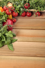 Herbs and vegetables with a blank wooden board for a copyspace