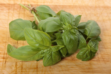 Bunch of fresh basil on an old wooden chopping board