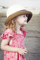 Little girl standing on the beach wearig big hat