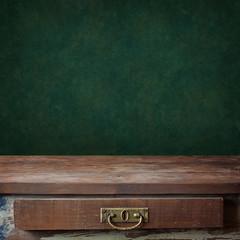 пустой деревянный стол с ящиком на фоне зеленой стены