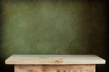пустой деревянный стол на фоне зеленой стены
