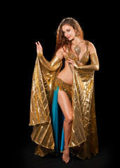 Young belly dancer posing in gold costume with Isis wings