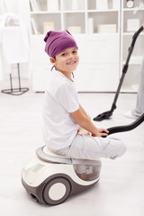 Young boy sitting on vacuum cleaner